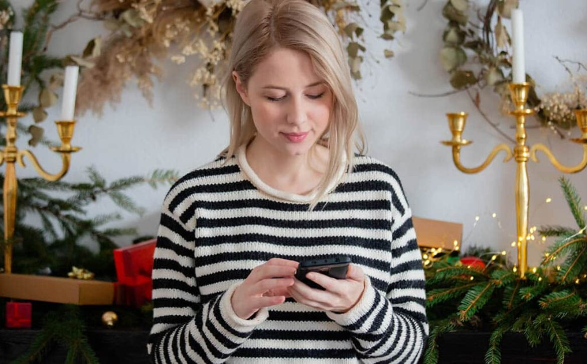 Beautiful woman with mobile phone near Christmas decorated fire
