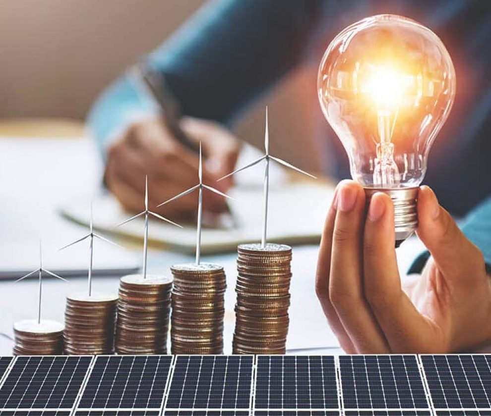businesswoman holding light bulb with turbine on coins and solar