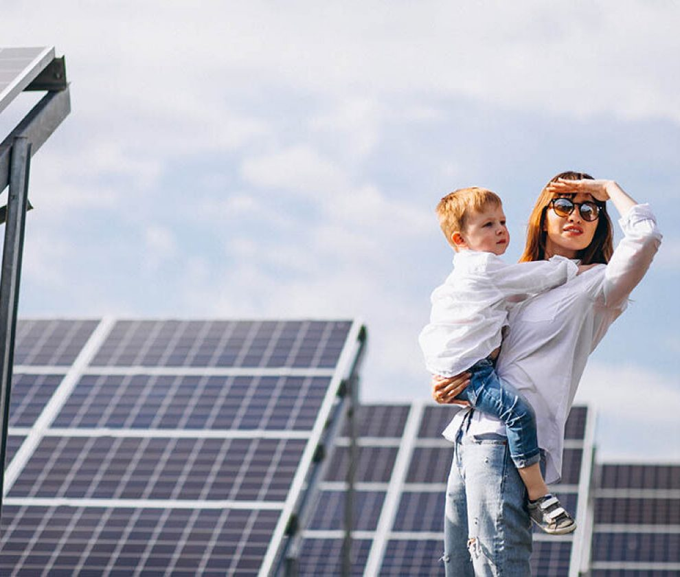 Mother with her little son by solar panels